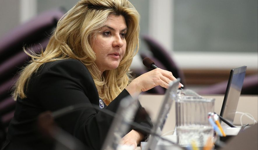 FILE - In this June 3, 2013, file photo,  Nevada Assemblywoman Michele Fiore, R-Las Vegas, works in committee during the final day of the 77th Legislative session at the Legislative Building in Carson City, Nev. Taxation Committee Chairwoman Michele Fiore broke her weeklong silence about dozens of tax liens filed against her and her companies, saying an unnamed employee who stole from her and systematically deceived her accountant was at the root of the problem. Fiore, a sophomore Republican lawmaker and Assembly majority leader, told conservative radio host Alan Stock on Tuesday, Dec. 16, 2014, that she has addressed the issue. She also argued that her experience working with the IRS though the resolution process is a reason she should retain her leadership on the tax committee. (AP Photo/Cathleen Allison, File)