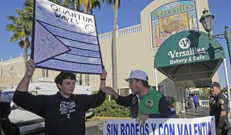 Anti-Castro protester Lazaro Lozano, right, argues with pro-Obama supporter Bryan Medina, left, in the Little Havana area of Miami, Wednesday, Dec. 17, 2014. Lozano expressed his disagreement with a surprise move announced by senior Obama administration officials that could pave the way for a major shift in U.S. policy toward the communist island nation, as Medina, who supports the move, looks on. (AP Photo/Alan Diaz)