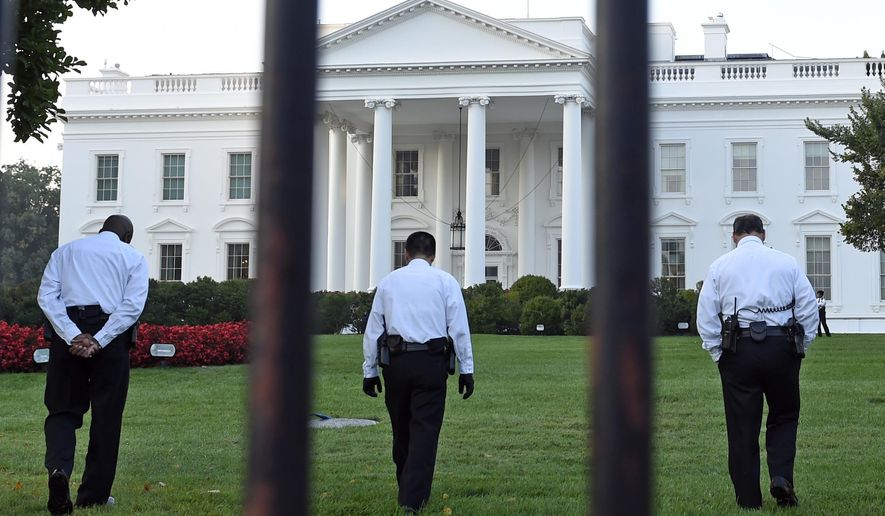 In this Sept. 20, 2014, file photo, uniformed Secret Service officers walk along the lawn on the North side of the White House in Washington. (AP Photo/Susan Walsh, File)