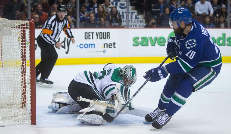 Dallas Stars' goalie Kari Lehtonen, left, of Finland, stops Vancouver Canucks' Chris Higgins on a breakway during the first period of an NHL hockey game in Vancouver,British Columbia, on Wednesday, Dec. 17, 2014. (AP Photo/The Canadian Press, Darryl Dyck)