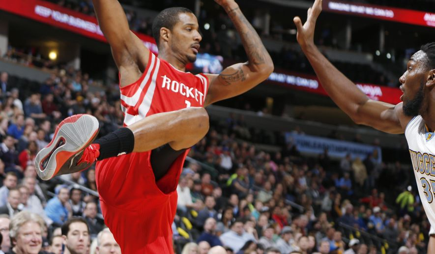 Houston Rockets forward Trevor Ariza, left, pulls in a loose ball as Denver Nuggets forward Kenneth Faried watches during the first quarter of an NBA basketball game Wednesday, Dec. 17, 2014, in Denver. (AP Photo/David Zalubowski)