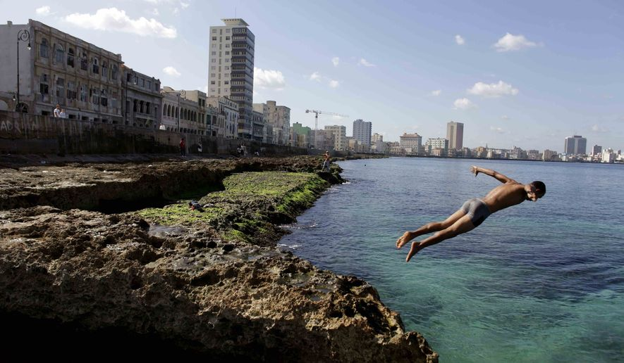 In this Nov. 28, 2011, file photo, a boy jumps into the water at the Malecon in Havana. While President Barack Obama announced Wednesday, Dec. 17, 2014, plans to restore diplomatic ties with the Caribbean island nation, it doesn't mean globe-trotting American tourists can hop on a plane to Havana anytime soon. It still remains illegal for most U.S. citizens to travel to, and spend money in, Cuba. (AP Photo/Javier Galeano, File)