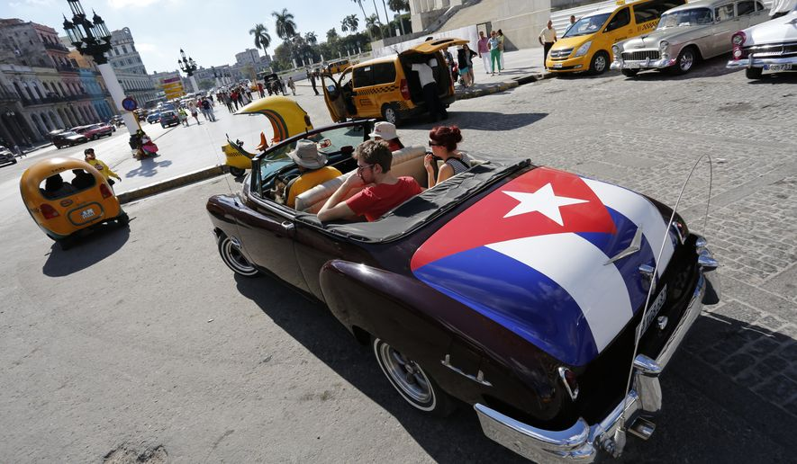 Tourists take a ride in a classic American convertible car with the Cuban national flag painted on the trunk, in Havana, Cuba, Thursday, Dec. 18, 2014. After a half-century of Cold War acrimony, the United States and Cuba abruptly moved on Wednesday to restore diplomatic relations, a historic shift that could revitalize the flow of money and people across the narrow waters that separate the two nations. (AP Photo/Desmond Boylan)