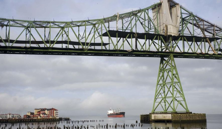 FILE--In this Oct. 15, 2012, file photo, a freighter is visible under the Astoria-Megler bridge in Astoria, Ore.  Ships drop more than just their anchors when they settle into the Astoria Anchorage, giving the economy a boost as crews hit dry land for supplies.(AP Photo/The Daily Astorian, Alex Pajunas, file)
