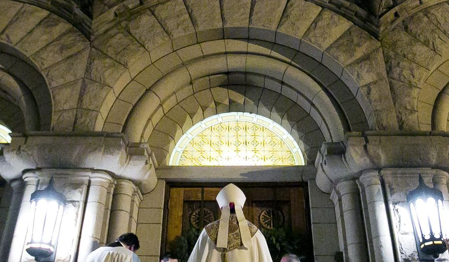 The Rev. Peter F. Christensen knocks on the doors of St. John's Cathedral and is welcomed into the cathedral where ceremonies began Tuesday Dec. 16, 2014 for his installation as new bishop of the Roman Catholic Diocese of Boise. (AP Photo/The Idaho Statesman, Darin Oswald)
