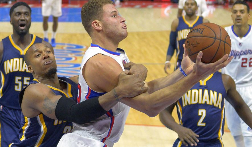 Los Angeles Clippers forward Blake Griffin, center, tries to put up a shot as Indiana Pacers forward David West, second from left, fouls him and center Roy Hibbert, left, guard Rodney Stuckey, second from right, and forward Matt Barnes, right, watch during the first half of an NBA basketball game, Wednesday, Dec. 17, 2014, in Los Angeles. (AP Photo/Mark J. Terrill)