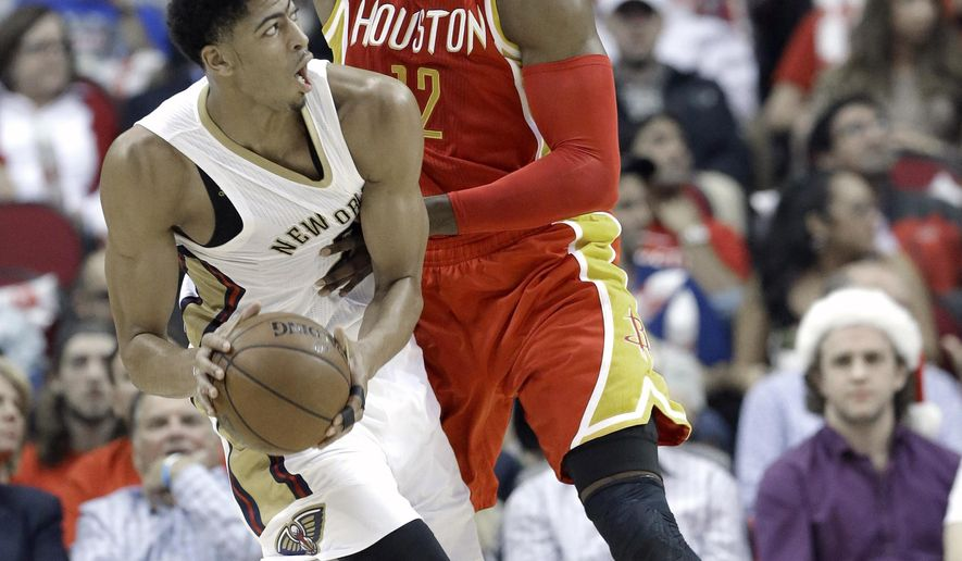 New Orleans Pelicans' Anthony Davis, left, is fouled by Houston Rockets' Dwight Howard (12) during the first half of an NBA basketball game Thursday, Dec. 18, 2014, in Houston. (AP Photo/Pat Sullivan)
