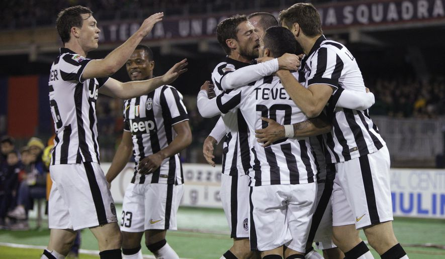 Juventus' Carlos Tevez, second from right,  celebrates after scoring during an Italian Serie A soccer match between Cagliari and Juventus, at the Sant' Elia stadium in Cagliari, Italy, Thursday, Dec. 18, 2014. (AP Photo/Daniela Santoni)