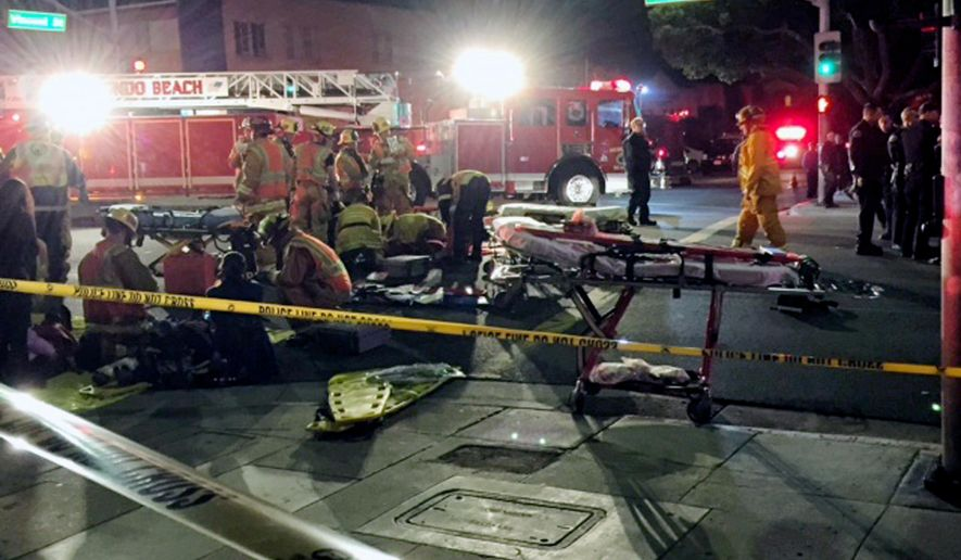 In this Wednesday, Dec. 17, 2014 photo provided by Mike Lewis, firefighters attend to a victim after a driver suspected of being intoxicated hit a group of pedestrians outside a church as a Christmas service ended in the Los Angeles suburb of Redondo Beach, Calif. Three people were killed and several others were injured including five children, police said. Margo Bronstein, 56, was arrested after the crash Wednesday night on suspicion of driving under the influence and vehicular manslaughter, Redondo Beach police Lt. Shawn Freeman said. (AP Photo/Mike Lewis)
