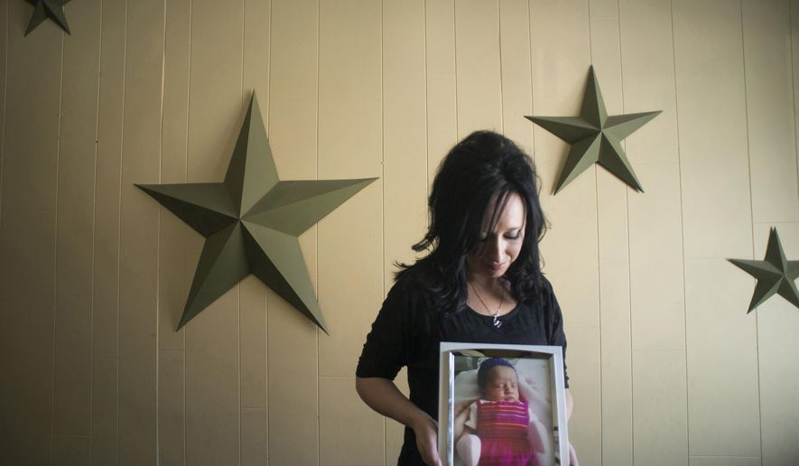 In this Nov. 13, 2014, photo, Jennifer Blaz, 34, poses for a photo in her home in Butte, Mont., holding a photograph of her daughter, Mattisyn Blaz.Matthew Blaz, 33, was sentenced to life in prison without parole for the death of their infant daughter. (AP Photo/Lido Vizzutti)