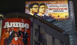 """In this Wednesday, Dec. 17, 2014, file photo, a banner for """"The Interview"""" is posted outside Arclight Cinemas in the Hollywood section of Los Angeles. (AP Photo/Damian Dovarganes, File)"""
