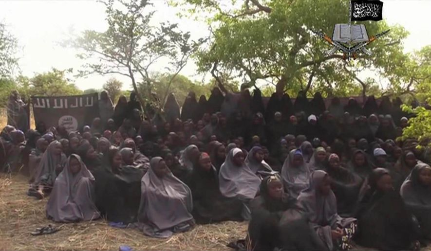 """FILE - This Monday May 12, 2014 file image taken from video by Nigeria's Boko Haram terrorist network, shows the alleged missing girls abducted from the northeastern town of Chibok. Islamic extremists killed 35 people and kidnapped at least 185, fleeing residents said Thursday of an attack near the town where nearly 300 schoolgirls were taken hostage in April. Teenager Aji Ibrahim said he was lucky to escape into the bushes. """"No doubt they were Boko Haram members because they were chanting """"Allahu akbar"""" (God is Great) while shooting at people and torching houses,"""" he told The Associated Press. (AP Photo/File)"""