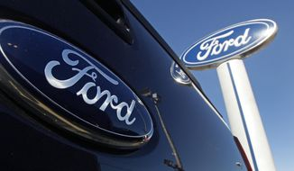 This Oct. 25, 2011, file photo, shows a Ford logo,on the tailgate of a pick-up truck, and on a Ford dealership sign at Salem Ford in Salem, N.H. (AP Photo/Charles Krupa, File)