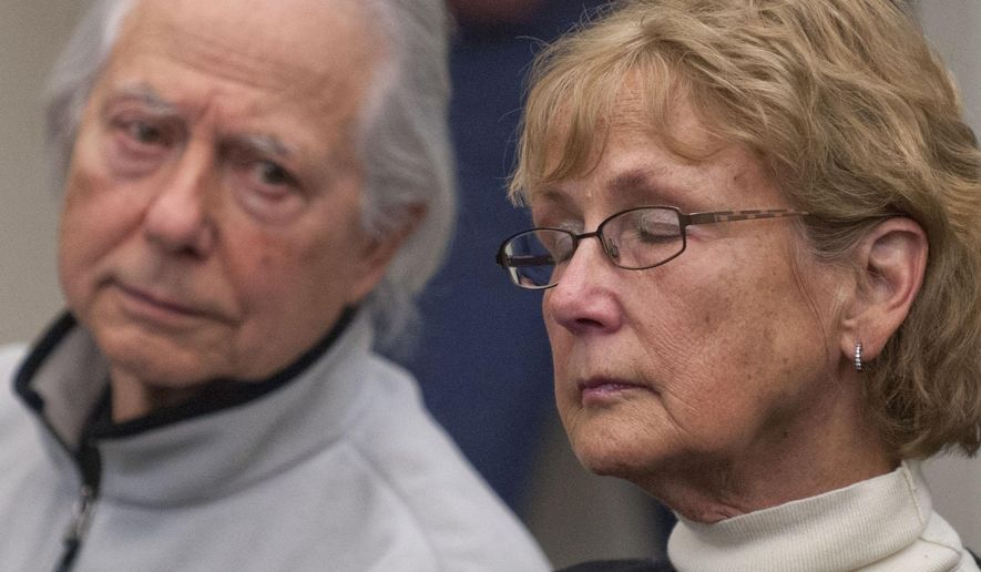 Jerry and Gail Battaglia listen during a police press conference Friday, Dec. 19, 2014, in Grand Rapids, Mich., about an arrest made in the 1990 murder of their son Christopher Joel Battaglia. Authorities say a 56-year-old man has been arrested in the death of Battaglia. The man is among four people charged in October with lying to investigators about the investigation. (AP Photo/The Grand Rapids Press, Chris Clark) ALL LOCAL TELEVISION OUT; LOCAL TELEVISION INTERNET OUT