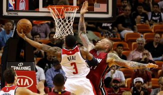 Washington Wizards guard Bradley Beal (3) is fouled by Miami Heat forward Chris Andersen (11) in the first half of an NBA basketball game, Friday, Dec. 19, 2014, in Miami. (AP Photo/Joe Skipper)