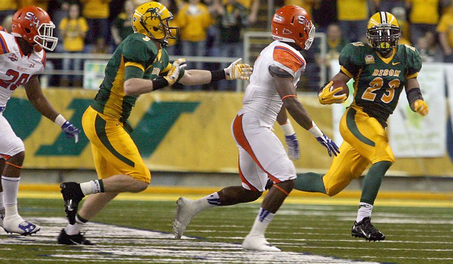 North Dakota State back John Crockett, right, runs a sweep against Sam Houston State defenders in the first half in the semifinals of the NCAA Football Championship Subdivision, Friday, Dec. 19, 2014, in Fargo, N.D. (AP Photo/Bruce Crummy)