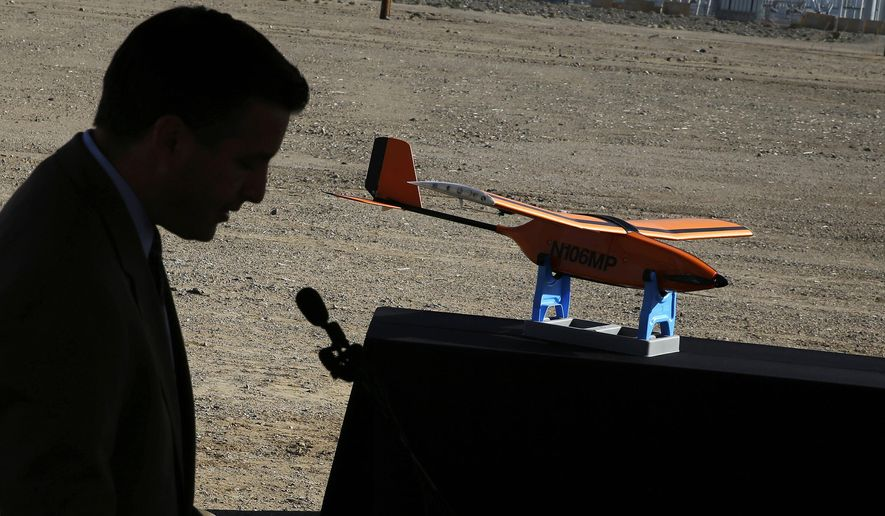 Nevada Governor Brian Sandoval speaks at an event to announce the FAA's first issuance of an unmanned aerial systems test site special airworthiness certificate Friday, Dec. 19, 2014, near Boulder City, Nev. Behind him is the Sensurion Aerospace Magpie commercial drone. (AP Photo/John Locher)