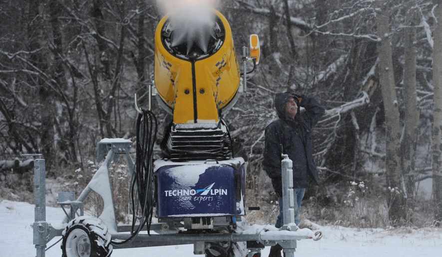FILE - Peter Zug of the Nordic Ski Association of Anchorage trail maintenance crew looks up after making an adjustment to a snow gun during a snowmaking test at Kincaid Park in this Monday, Dec. 1, 2014 file photo. With just days to go until solstice Sunday (Dec. 21) signals the official start of winter, bare ground can be seen in places and temperatures have been averaging in the 30s, prompting a few hardy residents to take to the streets in T-shirts and shorts.(AP Photo/Alaska Dispatch News, Bill Roth)