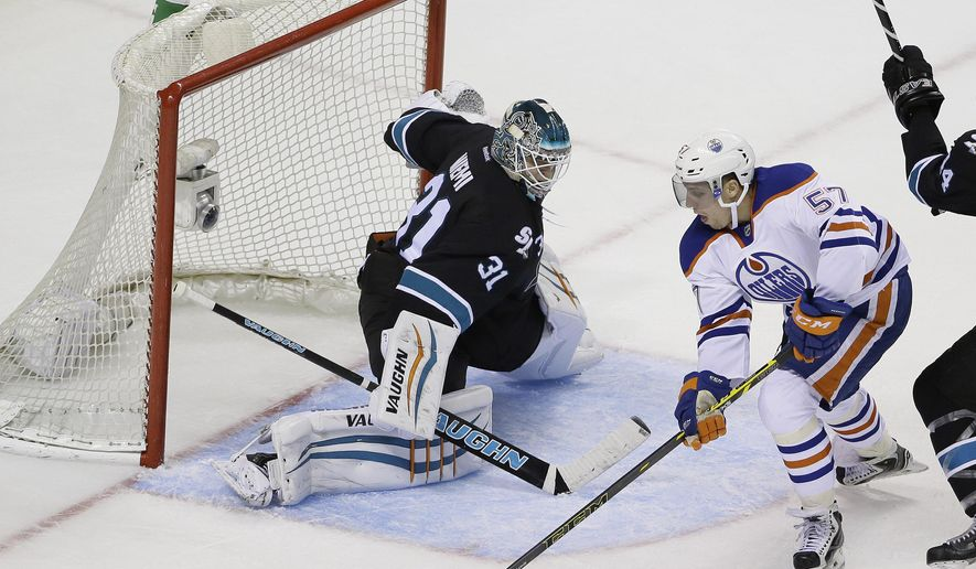 Edmonton Oilers left wing David Perron (57) tries to get the puck past San Jose Sharks goalie Antti Niemi (31) during the third period of an NHL hockey game Thursday, Dec. 18, 2014, in San Jose, Calif. San Jose won 4-3. (AP Photo/Eric Risberg)