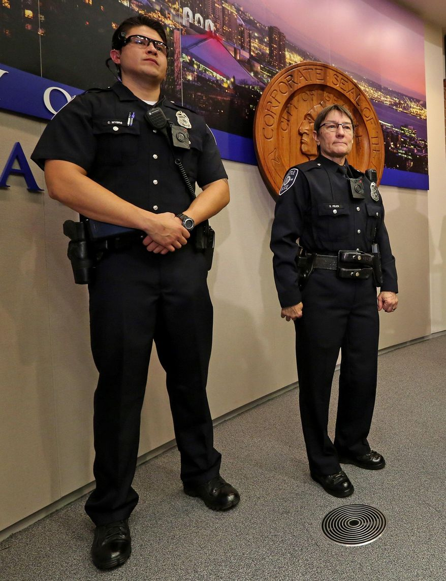 Seattle Police Officers Chris Myers, left, Debra Pelich stand with the department's new uniforms during a news conference in Seattle on Thursday, Dec. 18, 2014. (AP Photo/The Seattle Times, Greg Gilbert)