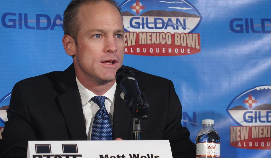 Utah State coach Matt Wells talks to reporters Friday, Dec. 19, 2014, in Albuquerque, N.M. Utah State is set to square off with UTEP and its run-heavy offense to launch the college football postseason Saturday at the New Mexico Bowl. (AP Photo/Russell Contreras)