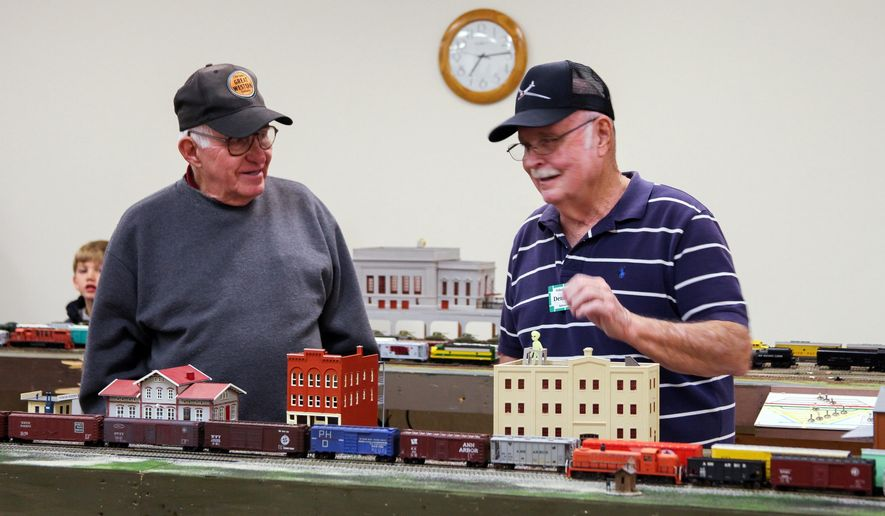 ADVANCE FOR WEEKEND EDITIONS, DEC. 20-22- In a photo from Dec. 3, 2014, Phil Lagnscon, 82, left, and Denny Tiggleman, 70, share stories about model trains during the Holland Modular Railroad Club's 2014 Christmas Train Show at Howard Miller Library in Zeeland, Mich. (AP Photo/The Holland Sentinel, Koly Swistaki)