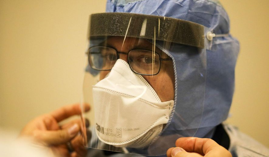 FILE - In this Tuesday, Oct. 28, 2014 file photo, Allina paramedic Jake Shepard gets help putting on a face shield as Allina EMS first responders receive training on the latest protocol for handling future patients possibly infected with Ebola in Mounds View, Minn.  The Ebola outbreak in West Africa hit home in Minnesota, which shelters one of the largest Liberian communities in the U.S. Health officials began monitoring travelers returning from the affected countries this fall and four Minnesota hospitals became designated treatment centers. (AP Photo/The Star Tribune, David Joles, File)