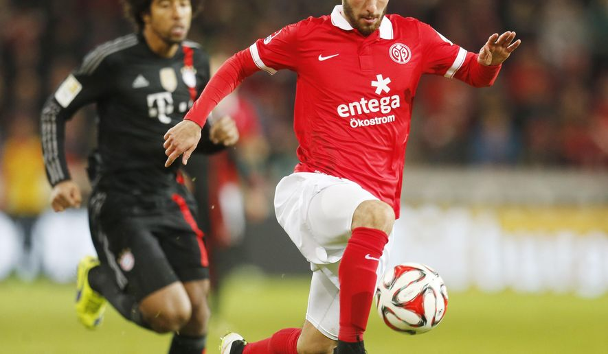 Mainz's Yunus Malli, right, and Bayern's Dante from Brazil challenge for the ball during the German first division Bundesliga soccer match between FSV Mainz 05 and Bayern Munich in Mainz, Germany, Friday, Dec.19, 2014. (AP Photo/Michael Probst)