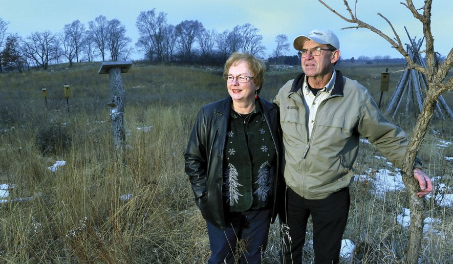 In this photo taken on Dec. 14, 2014, Marti and Ron Martin stand on the winter-time prairie that they created around their home in rural Milton, Wis..  More than 20 years ago, the Martins turned a love of nature into one of the area's first land restoration businesses. (AP Photo/The Janesville Gazette, Bill Olmsted)