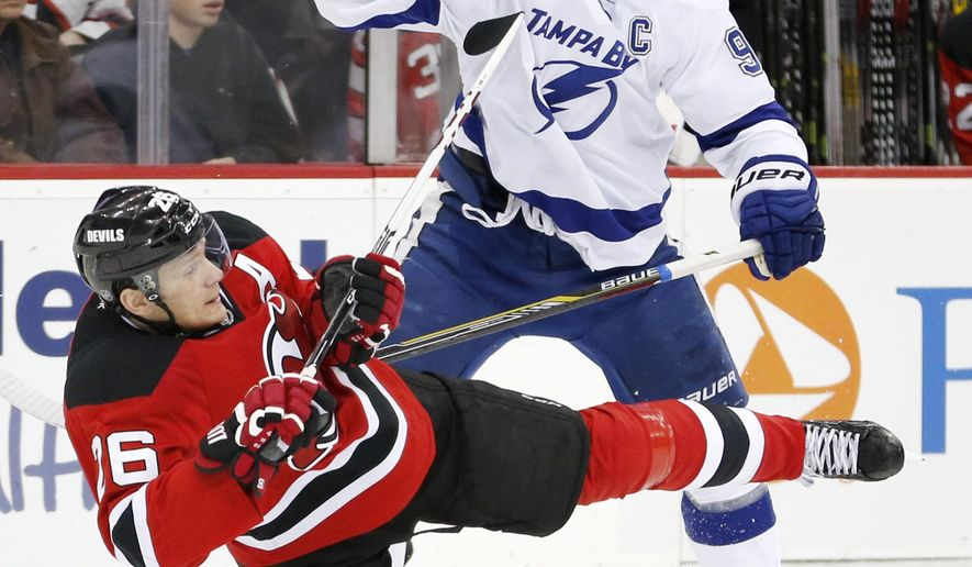 New Jersey Devils left wing Patrik Elias, bottom, of the Czech Republic, is checked by Tampa Bay Lightning center Steven Stamkos during the first period of an NHL hockey game, Friday, Dec. 19, 2014, in Newark, N.J. (AP Photo/Julio Cortez)