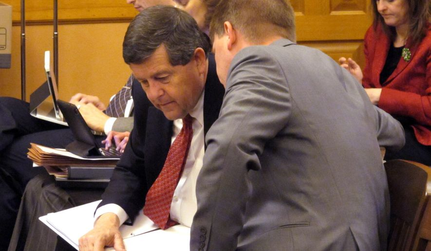 Alan Conroy, left, executive director of the Kansas Public Employees Retirement System, confers with Shawn Sullivan, right, Gov. Sam Brownback's budget director, during a legislative committee meeting on pension issues, Friday, Dec. 19, 2014, at the Statehouse in Topeka, Kan. Sullivan is proposing that Kansas study privatizing the state pension system. (AP Photo/John Hanna)
