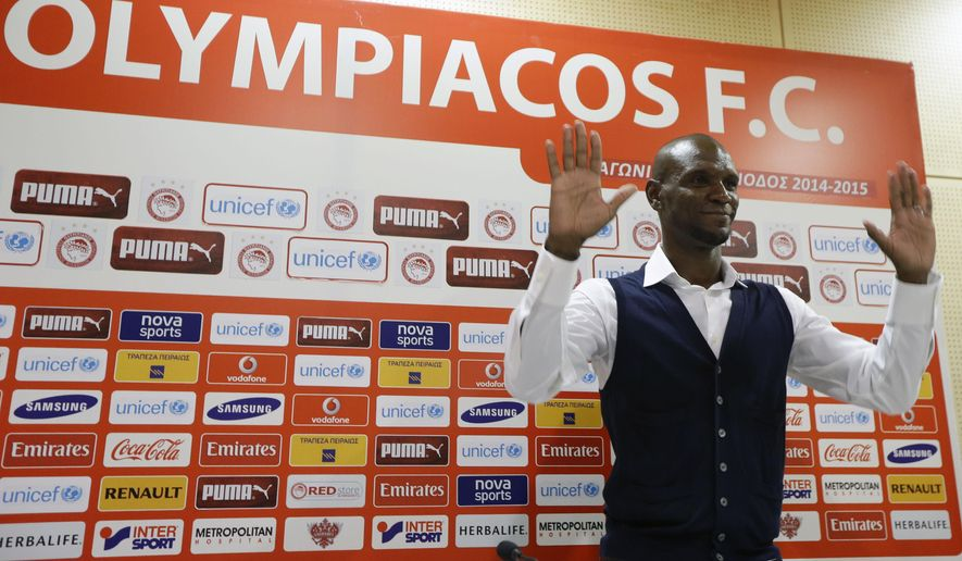 Olympiakos soccer player Eric Abidal gestures to photographers after a press conference at the Georgios Karaiskakis stadium in Piraeus, the port of Athens, on Friday, Dec. 19, 2014. Frenchman Abidal, 35, a defender who twice won the Champions League with Barcelona and played for France 67 times, announced his retirement for personal reasons after a 15-year career. He signed up with Olympiakos in July. (AP Photo/Thanassis Stavrakis)