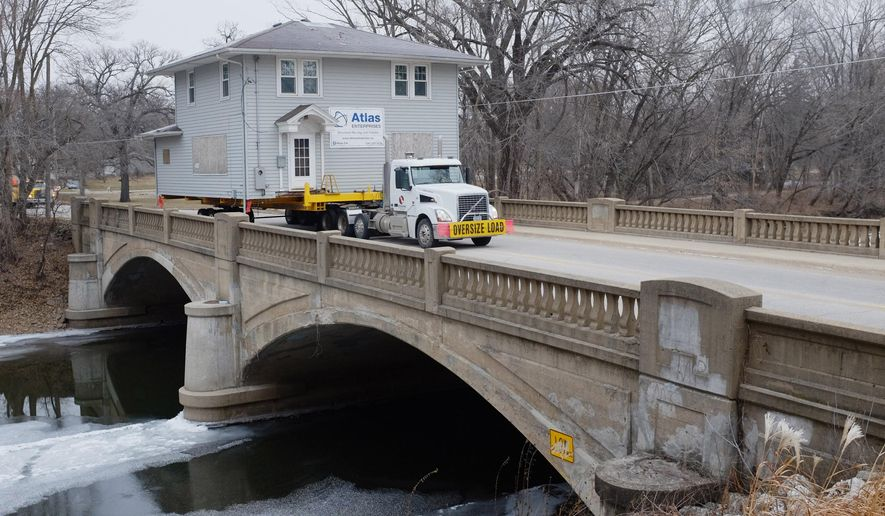 In this photo taken Thursday, Dec. 18, 2014, Forest City, Iowa, based Atlas Enterprises moves one of the Mason City, Iowa, flood houses across a 100-year-old bridge on North Carolina Avenue.  (AP Photo/The Globe Gazette, Arian Schuessler)