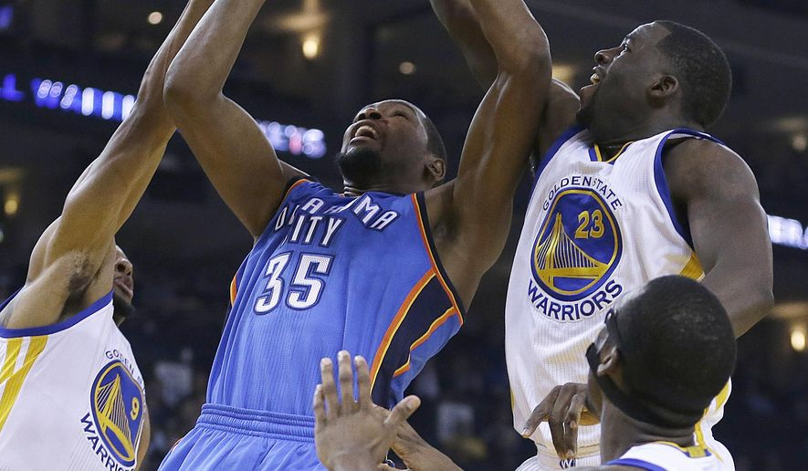 Oklahoma City Thunder forward Kevin Durant (35) shoots between Golden State Warriors' Andre Iguodala, left, and Draymond Green (23) during the first half of an NBA basketball game Thursday, Dec. 18, 2014, in Oakland, Calif. (AP Photo/Ben Margot)