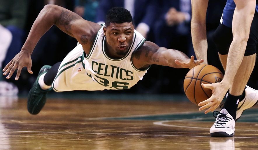 Boston Celtics guard Marcus Smart (36) dives as Minnesota Timberwolves forward Robbie Hummel picks up the loose ball during the second half of an NBA basketball game in Boston, Friday, Dec. 19, 2014. The Celtics defeated the Timberwolves 114-98. (AP Photo/Charles Krupa)