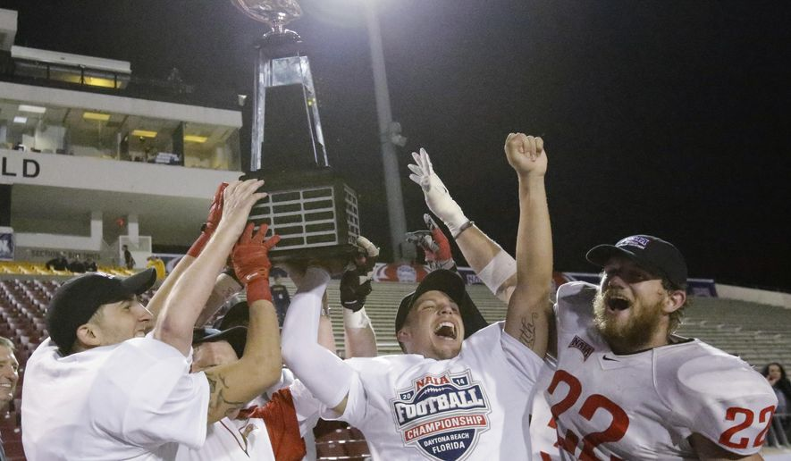 Southern Oregon players, including quarterback Austin Dodge, second from right, and linebacker Heston Altenbach (22), celebrate with the trophy after winning the NAIA championship football game against Marian, 55-31, in Daytona Beach, Fla., Friday, Dec. 19, 2014. (AP Photo/John Raoux)