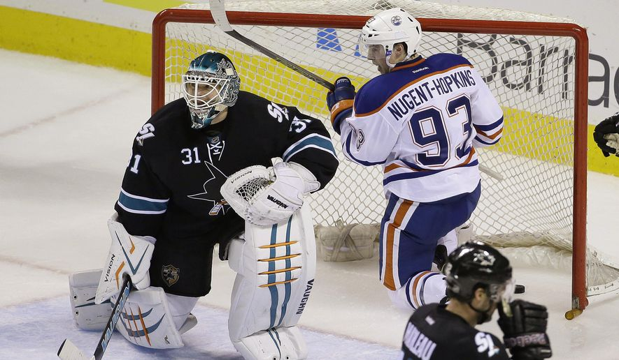 Edmonton Oilers center Ryan Nugent-Hopkins (93) reacts after scoring a goal against San Jose Sharks goalie Antti Niemi (31) during the second period of an NHL hockey game Thursday, Dec. 18, 2014, in San Jose, Calif. In the foreground is San Jose Sharks center Patrick Marleau. (AP Photo/Eric Risberg)