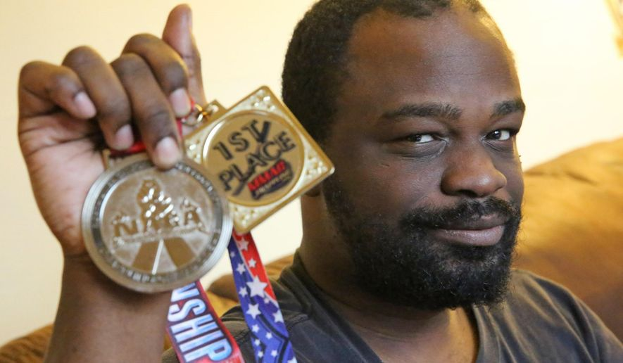 In this Dec. 17, 2014 photo, Jessie Roach, who has intellectual disabilities and was recently involved in an unregulated kick-boxing event at the Harley dealership on W. Silver Spring Dr., in Milwaukee, Wis., poses with his medals. After the Milwaukee Journal Sentinel included Roach's story in an article about unregulated combat sports in Wisconsin, several readers across the country have since sent Roach letters of encouragement, money and medals. (AP Photo/Milwaukee Journal-Sentinel, Mike De Sisti )