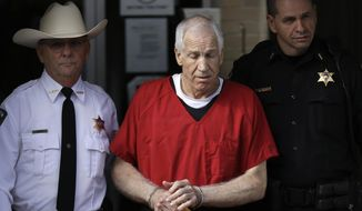 In this Oct. 9, 2012, file photo, former Penn State University assistant football coach Jerry Sandusky, center, is taken from the Centre County Courthouse by Centre County Sheriff Denny Nau, left, and a deputy, after being sentenced in Bellefonte, Pa. Sandusky lost a legal battle to restore his $4,900-a-month pension, a benefit that was canceled two years ago after he was sentenced for child molestation. (AP Photo/Matt Rourke, File)