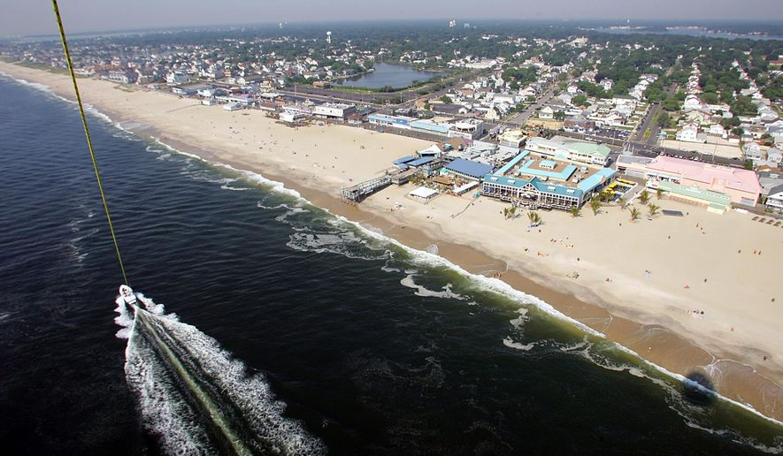 FILE - In this July 22, 2005, file photo, Jenkinson's Pavilion and the Boardwalk in Point Pleasant, N.J., seen in this photo taken while parasailing. The owners of Jenkinson's Pavilion filed a lawsuit on Dec. 16., 2014, against New Jersey, Point Pleasant Beach and the U.S. Army Corps of Engineers, claiming that easements required for a protective dune project being carried out by the Army Corps would effectively make the privately owned beach publicly owned. The lawsuit seeks a court ruling on exactly what government can do to private property as part of the beach project. (AP Photo/Tim Larsen)