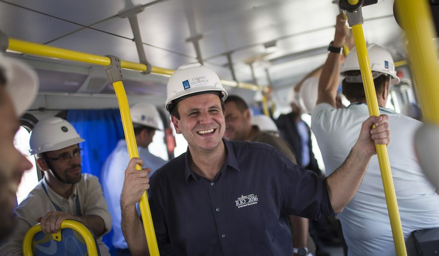 Mayor Eduardo Paes talks to journalists on a bus during his tour of Olympic Park in Rio de Janeiro, Brazil, Friday, Dec. 19, 2014. Rio will host the Olympic Games in 2016. (AP Photo/Felipe Dana)
