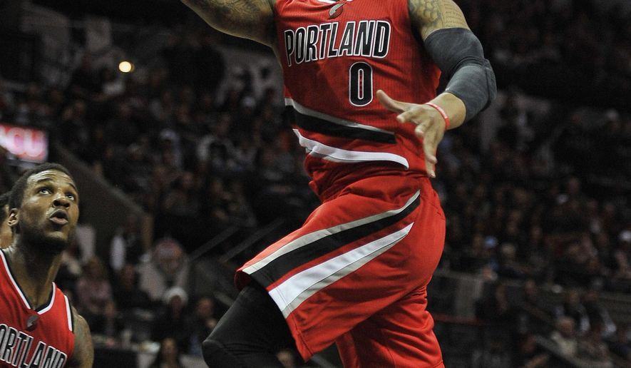 Portland Trail Blazers guard Damian Lillard shoots during the second half of an NBA basketball game against the San Antonio Spurs, Friday, Dec. 19, 2014, in San Antonio. (AP Photo/Darren Abate)
