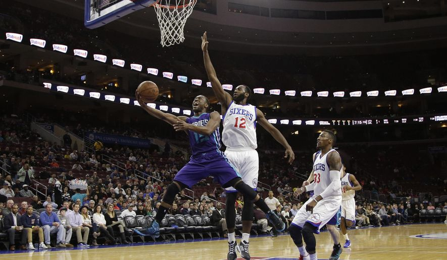 Charlotte Hornets' Kemba Walker (15) goes up for a shot past Philadelphia 76ers' Luc Mbah a Moute (12) and Robert Covington (33) during the first half of an NBA basketball game, Friday, Dec. 19, 2014, in Philadelphia. (AP Photo/Matt Slocum)