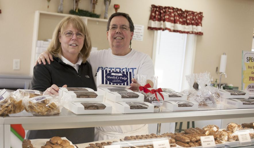 ADVANCE FOR USE MONDAY, DEC 22 - In this photo taken on Dec. 2, 2014, Marcy and John Murdick the new owners of the Original Murdick's Fudge shop, pose for aphoto in Frankenmuth, Mich. (AP Photo/The Saginaw News, Neil Barris) ALL LOCAL TELEVISION OUT; LOCAL TELEVISION INTERNET OUT MBO  (REV-SHARE)
