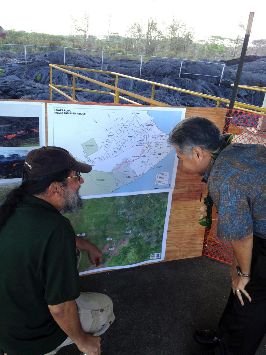 Hawaii Gov. David Ige looks at maps of the lava flow amid mounds of hardened lava at Pahoa Transfer Station on Hawaii's Big Island on Thursday, Dec. 18. (AP Photo/Courtesy Ryan Kalei Tsuji, senior special assistant to the governor)
