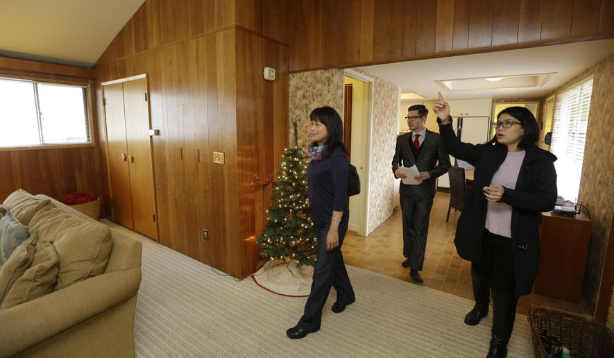 Debbie Lin, right, of Windermere Real Estate, speaks Manderin as she shows a home for sale to Amy Hsu, left, a real estate broker who was looking at homes on behalf of a client from China, Thursday, Dec. 18, 2014, in Bellevue, Wash., as fellow broker Josh Avery, center, walks behind them. Seattle-area real estate agents are taking note of growing connections linking China and Washington state, which ranks second to California in real estate sales to Chinese buyers. (AP Photo/Ted S. Warren)