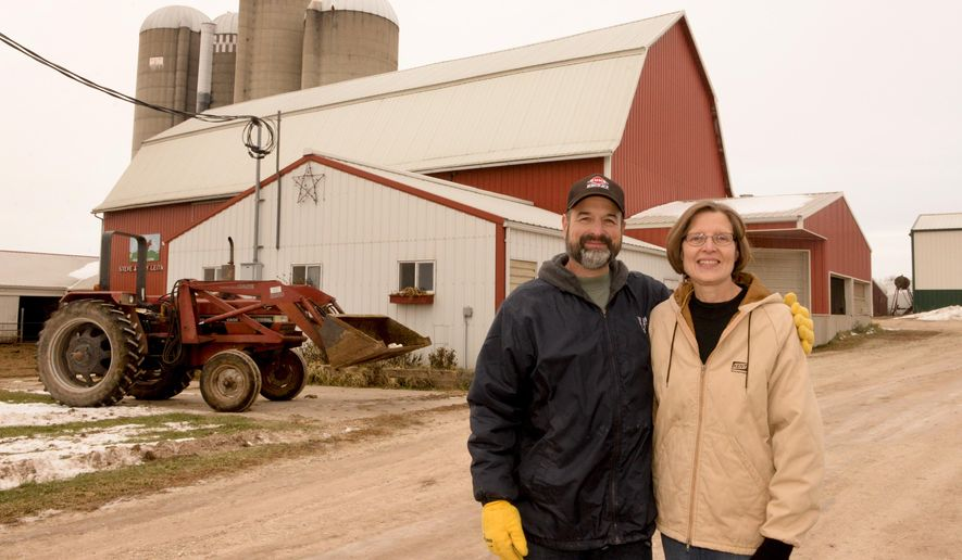 ADVANCE FOR USE MONDAY, DEC. 22 - In this photo taken on Dec. 4, 2014 Marsh Edge Dairy owner's Steve and Mary Leitner pose in front of their farm in Reedsville, Wis. The Leitners also use a computerized cart-feeding system that moves around the barn on a track, stopping at each cow and giving the appropriate amount of feed to each animal. The family has been using this system in their tie-stall barn since 1992. (AP Photo/Herald-Times Reporter,  Sue Pischke) NO SALES