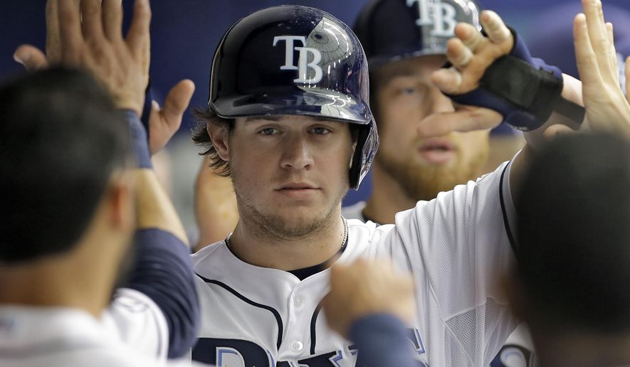 """FILE - In this Sept. 1, 2014, file photo, Tampa Bay Rays' Wil Myers, center, and Ben Zobrist, right, high-five teammates in the dugout after scoring on a two-run single by Evan Longoria off Boston Red Sox starting pitcher Rubby De La Rosa during the third inning of a baseball game  in St. Petersburg, Fla. The Rays, Padres and Nationals have finalized an 11-player trade that sent 2013 AL Rookie of the Year Wil Myers from Tampa Bay to San Diego and outfielder Steven Souza Jr. from Washington to the Rays. The deal was formally announced Friday, Dec. 19, 2014, two days after the Rays agreed to part with Myers in a move that team president Matt Silverman says will make Tampa Bay """"more competitive for 2015 and beyond.""""(AP Photo/Chris O'Meara, File)"""