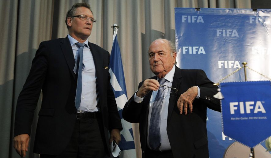 FIFA president Sepp Blatter and FIFA secretary general Jerome Valcke, left, leave after a press conference in Marrakech, Morocco, Friday, Dec. 19, 2014. FIFA will not reopen the vote for the 2018 and 2022 World Cups, and will publish at least some of the confidential report into the bidding process, President Sepp Blatter said Friday. (AP Photo/Christophe Ena)