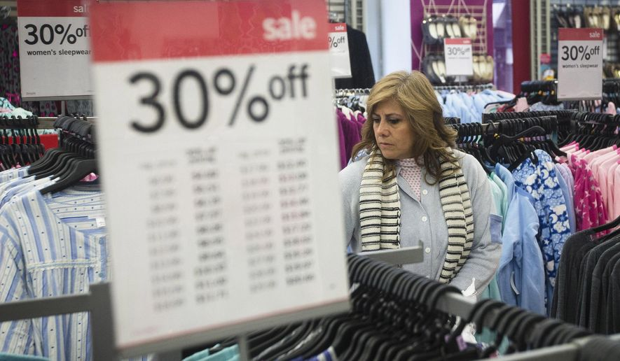 FILE - In this Thursday, Nov. 27, 2014 file photo, Giselle Basurto, of Mexico, shops at a Kmart store in New York on Thanksgiving Day. Retail sales rose 1.8 percent from Nov. 1 through Monday, Dec. 15, 2014 according to data provided from First Data Corp., which tracks purchases at 800,000 stores including online. The modest growth comes despite the heavy discounting customary throughout the season. (AP Photo/John Minchillo)